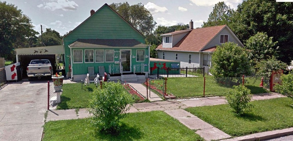 Front yard enclosure, bright house colors, horse figurines, and hand-painted artwork